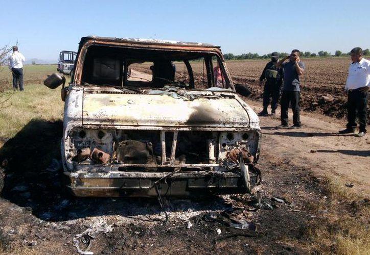 Las autoridades del estado de Sinaloa iniciaron los exámenes necesarios para identificar los cuerpos localizados al interior de esta camioneta, la cual se confirmó que estaba registrada a nombre de Adam Coleman. (AP)
