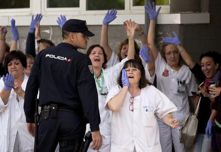 Practicantes de medicina gritan consignas contra el Primer Ministro de España, Mariano Rajoy, durante su visita al hospital Carlos III en Madrid, donde una auxiliar de enfermería se infectó con el virus del ébola. (Foto: AP)