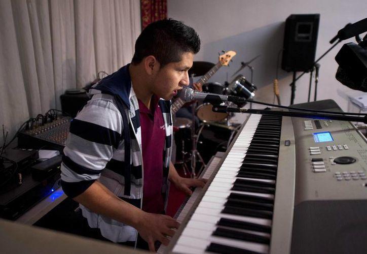 Marvin Velasco practica música en su iglesia en Los Ángeles, California, el lunes, 11 de enero de 2016. Marvin, quien fue víctima de abuso por parte de un pariente, vive ahora con una familia guatemalteca que lo trata como a su hijo. (AP J de Foto/Señal. Terrill)