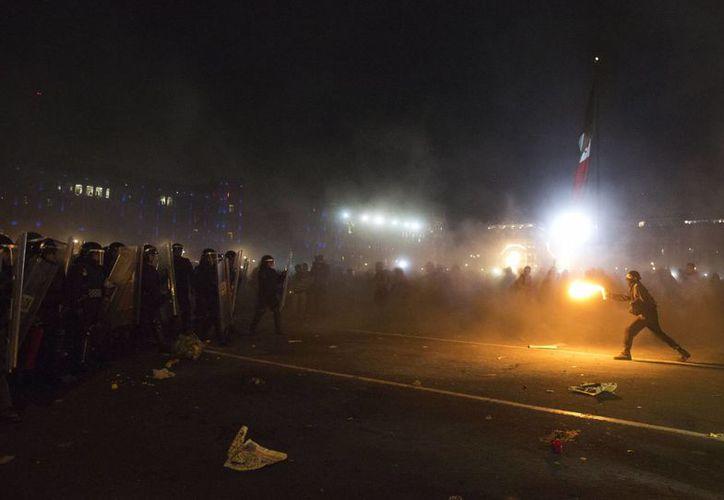 Los manifestantes se enfrentaron anoche contra la policía en el Zócalo de la Ciudad de México. (Agencias)