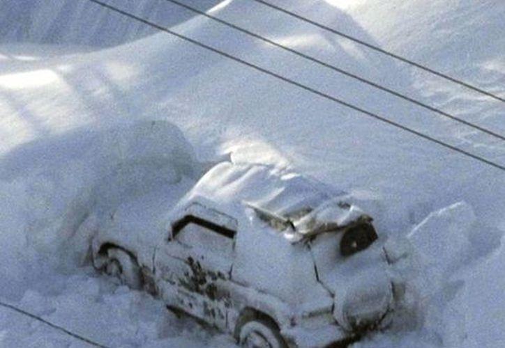 Vehículos varados y sepultados bajo la nieve en Nakashibetsu, norte de Japón. (AP)
