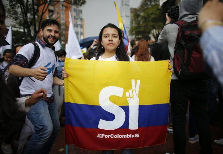 """Una estudiante muestra una bandera de Colombia promoviendo el voto por el """"sí"""" para el próximo plebiscito sobre el acuerdo de paz firmado entre el gobierno y los rebeldes de las FARC. (AP/Ariana Cubillos)"""