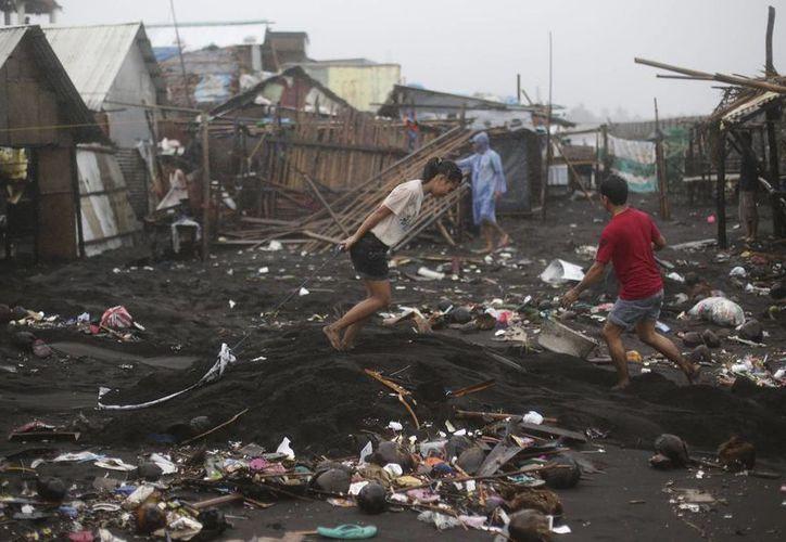 Residentes comienzan a limpiar sus casas después de las fuertes olas del tifón Hagupit en Legazpi, provincia de Albay, Filipinas oriental. (Agencias)