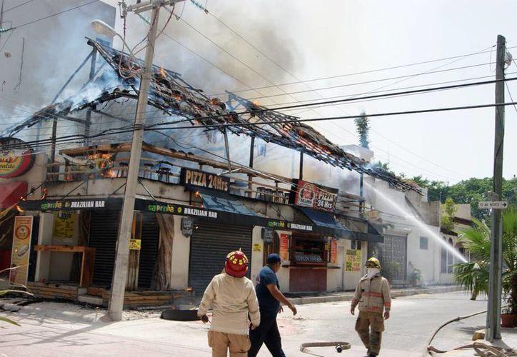 El incendio de una palapa en la zona turística de Playa del Carmen, provocó el cierre de un tramo de la Décima Avenida. (Octavio Martínez/SIPSE)