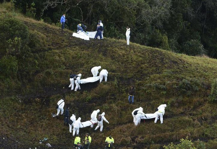Imagen de los rescatistas mientras se llevan los cuerpos de las víctimas del avionazo, en las afueras de Medellín, Colombia. (AP Photo/Luis Benavides)