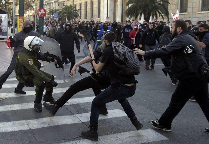 Estudiantes se enfrentan a la policía durante una manifestación en recuerdo al asesinato de Alexandros Grigoropoulos, de 15 años, por disparos de la policía en las calles de Atenas. (EFE)