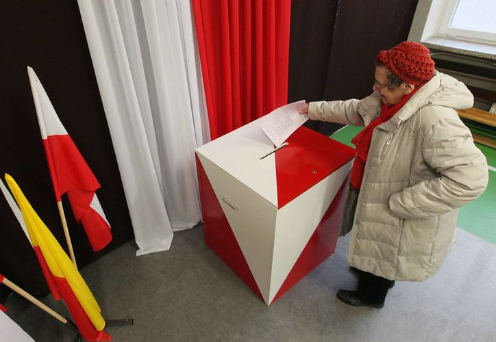 Una mujer deposita su voto en la primera ronda de las elecciones locales en Varsovia, Polonia. (Agencias)