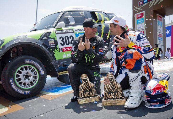 Stephane Peterhansel (i) y Cyril Despres, de Francia, en el podio tras ganar en las categorías de coches y motocicleta, respectivamente del Rally Dakar 2013. (Agencias)