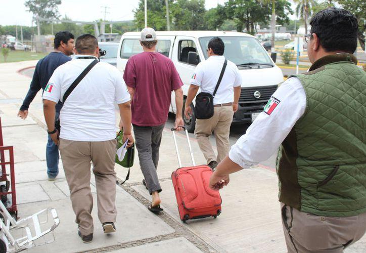 El ciudadano fue subido a una camioneta tipo Van, blanca, con placas de circulación UTP-606-D propiedad del INM. (Joel Zamora/SIPSE)