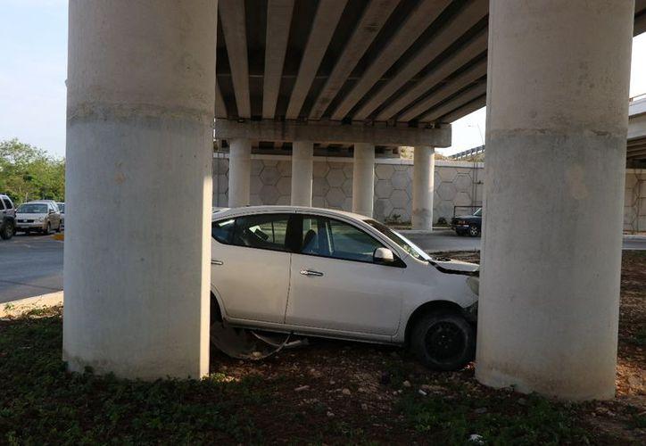La conductora del Versa placas 686-ZGC rodeó a exceso de velocidad la glorieta del paso a desnivel de entrada a Los Héroes y perdió el control del coche. (Fotos: Aldo Pallota/SIPSE)