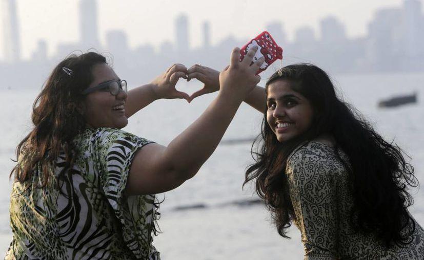 Las personas etiquetaron en Twitter la palabra 'amor' en 12 idiomas distintos más de dos mil 500 millones de veces. Dos mujeres se toman una selfie mientras hacen un corazón con sus manos para celebrar el día de San Valentín. (AP/Rajanish Kakade)