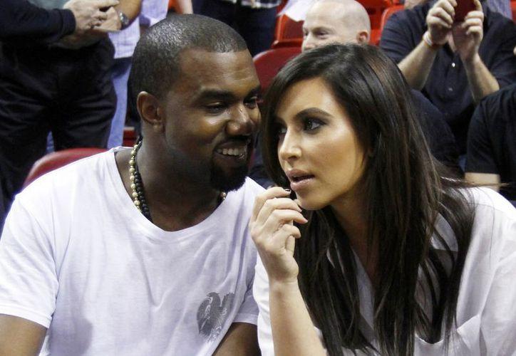 Kanye West platica con su novia Kim Kardashian antes de un juego de la NBA en Miami. (Agencias)