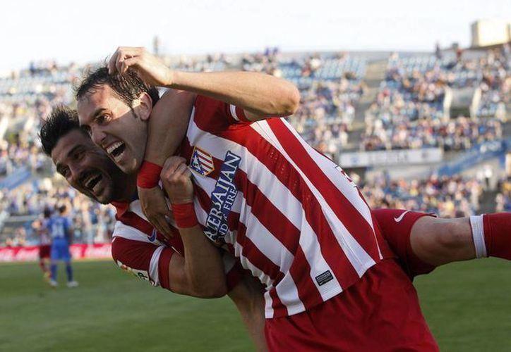 El defensa uruguayo Diego Godín (d) celebra con el goleador David Villa el gol que metió para el Atlético de Madrid ante Getafe. (EFE)