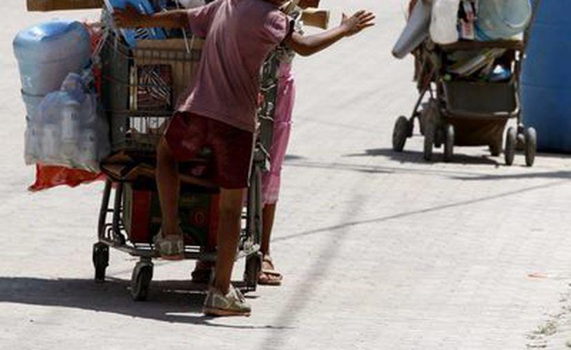 """Los niños """"recogelatas"""" recorren los arenales de Playa del Carmen sin alguna protección. (Adrián Monroy/SIPSE)"""