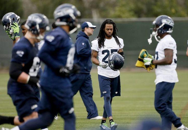 Richard Sherman, de Seahawks, se pone su casco en un entrenamiento previo al Super Bowl contra Patriots. (Foto:AP)