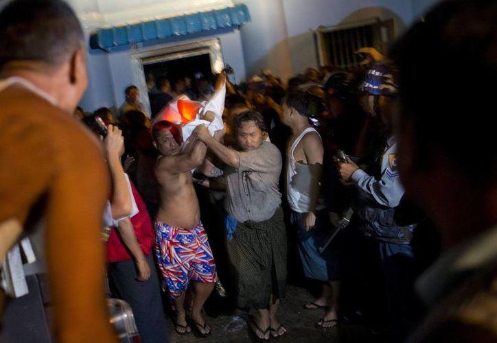 Voluntarios retiran una bolsa con el cuerpo de una de las víctimas mortales de la mezquita de Yangón. (AP)