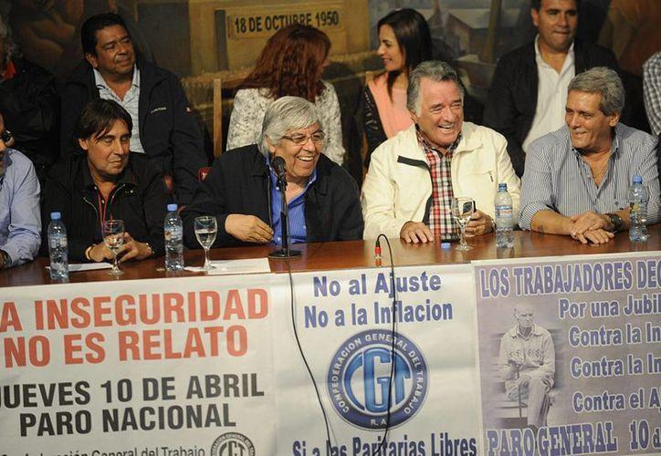 Hugo Moyano (c), cabeza del poderoso sindicato de camioneros, habla junto a uno de los dirigentes sindicales convocantes de la huelga, Luis Barrionuevo (2d). (EFE)