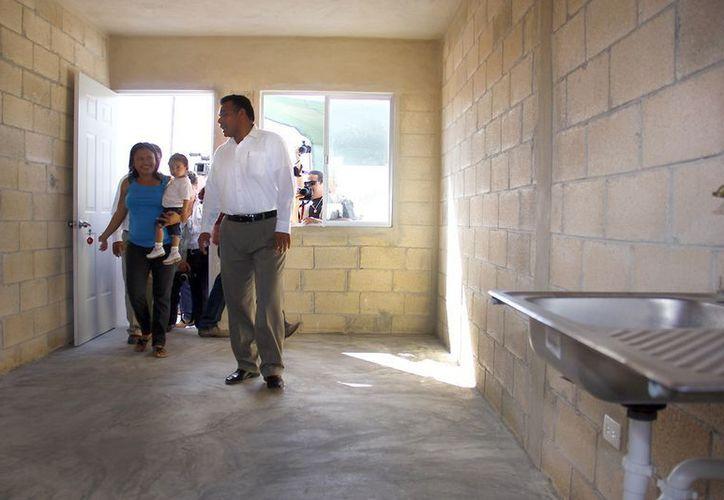 El gobernador Rolando Zapata muestra su nuevo hogar a una familia. (Milenio Novedades)