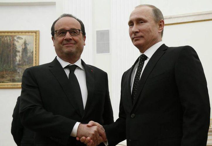 El presidente ruso, Vladimir Putin , a la derecha , estrecha la mano con su homólogo francés, François Hollande durante su reunión en Rusia, este el jueves 26 de noviembre de 2015. El  mandatario francés llegó a Moscú para presionar por una coalición más fuerte contra el Estado Islámico en Siria. (Foto AP/Alexander Zemlianichenko)