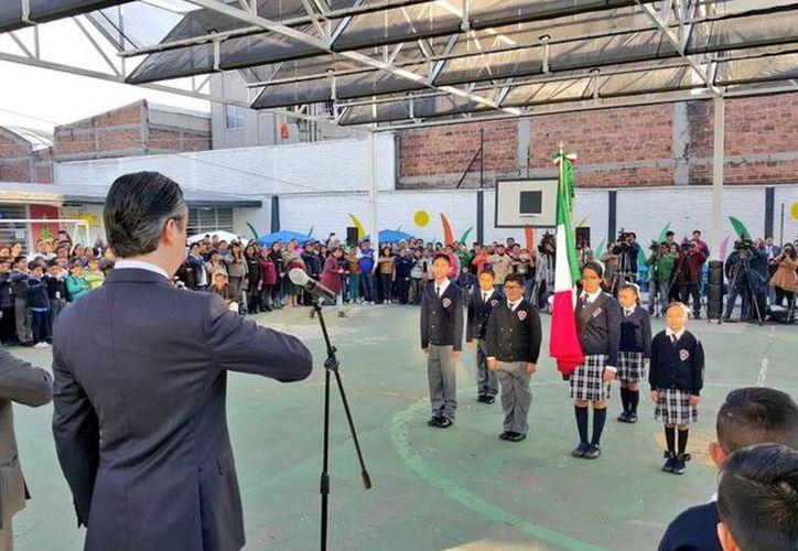 El secretario de Educación Pública, Aurelio Nuño Mayer (der), al rendir  honores a la Bandera en la Escuela Primaria Modelo, donde reconoció la participación de los maestros del país durante la evaluación docente. (twitter/@aurelionuno)