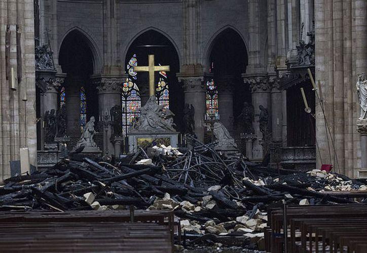 Montículos de material quemado ocupan los pasillos de la Catedral de Notre Dame este martes.  (Bloomberg)