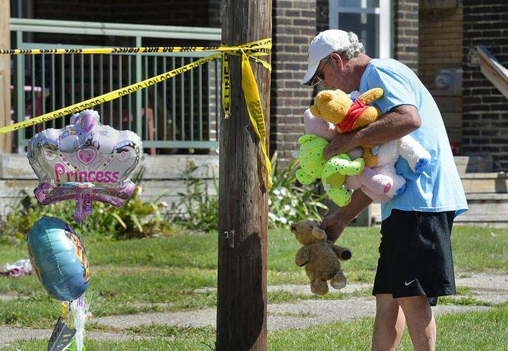 Un hombre coloca un muñeco de peluche en recuerdo de los pequeños fallecidos. (Greg Wohlford/Erie Times-News via AP)