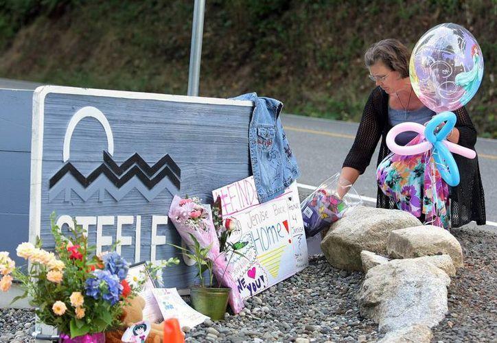 Karole Johnson coloca globos de princesas y flores a la entrada de un parque de casas rodantes en Bremerton, Washington, de donde desapareció la niña Jenise Wright. (Foto: AP)