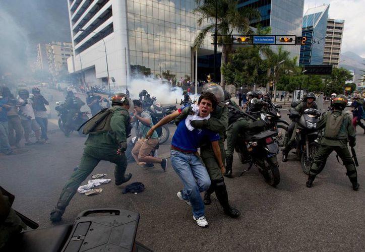 Policías reprimen a manifestantes en una protesta antiigubernamental en Caracas, Venezuela, este miércoles 14 de mayo de 2014. (Foto: Fernando Llano/AP)