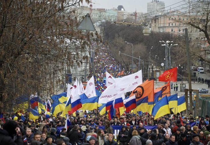 Manifestantes opositores a la intervención de Putin marchan en Moscú con banderas rusas y ucranianas. (Agencias)