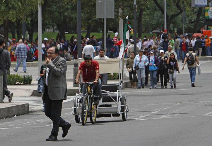 Un taxista de dos ruedas avanza paralelo a una calle bloqueada por maestros de la CNTE en el DF. (Agencias)