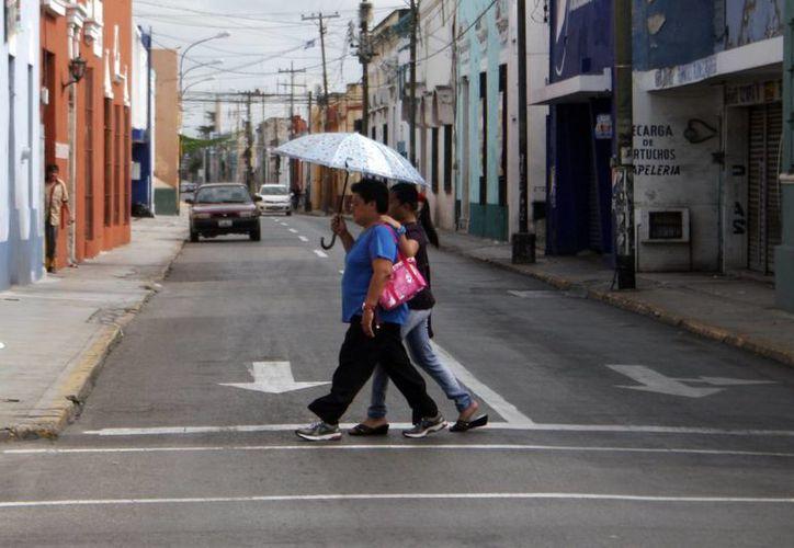 Ante la lluvia, muchos meridanos salieron a realizar sus labores protegidos con paraguas. (SIPSE)