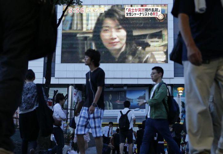 Una megapantalla en una avenida de Tokio muestra la fotografía de la periodista japonesa Mika Yamamoto, asesinada en medio de la violencia en Siria. (Agencias)