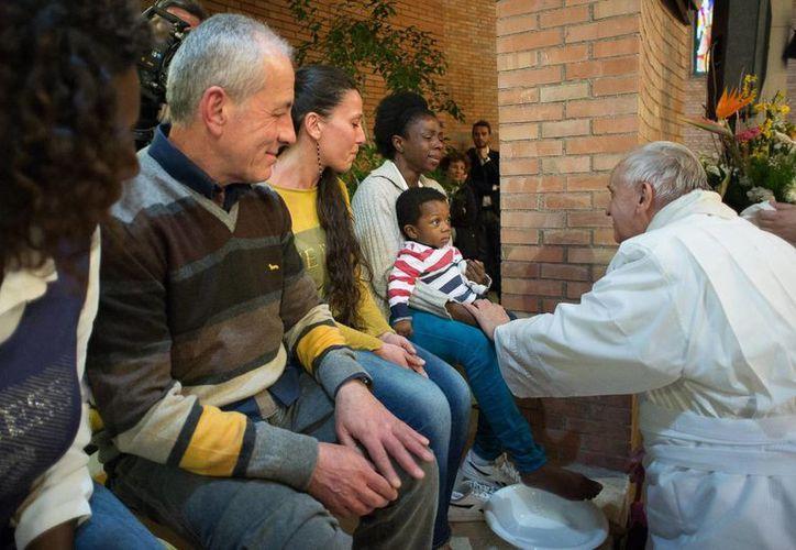 Francisco lavó incluso los pies al hijo de una interna que sostenía en brazos, en la capilla de la cárcel romana de Rebbibia. (Foto AP)