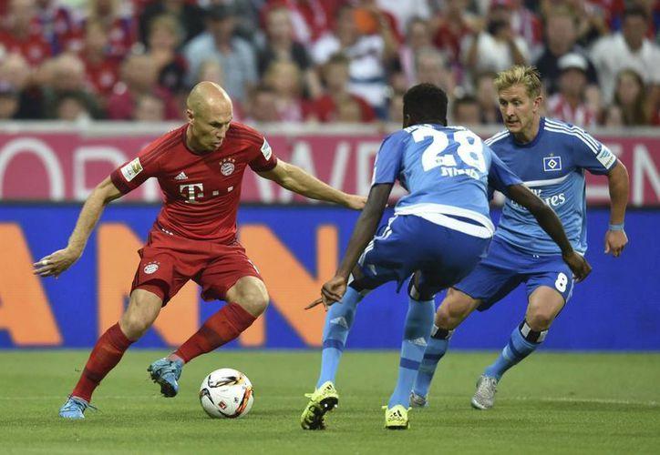 El jugador del Bayern de Múnich Arjen Robben lucha por el balón con Gideon Jung y Lewis Holtby del Hamburgo SV, durante el partido que ambos equipos disputan en el estadio Allianz Arena. (EFE)