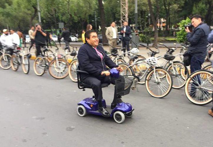 El senador Miguel Barbosa llegó a bordo de un scooter eléctrico, el cual aseguró, utiliza para transportarse en su casa o cuando va de paseo. (twitter/BarbosaMX)