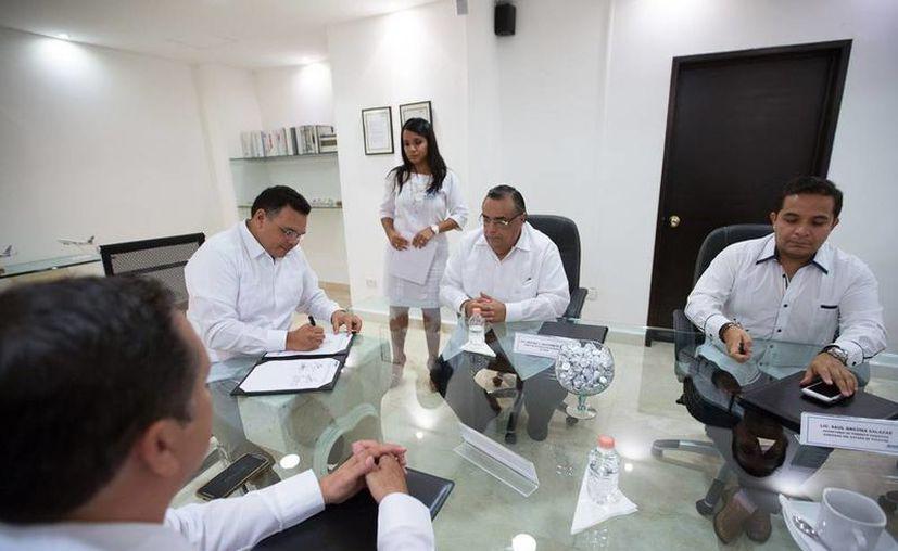 El gobernador, Rolando Zapata Bello, (a la izq., firmando), presidió la reunión del Consejo Consultivo del aeropuerto internacional de Mérida. (Cortesía)