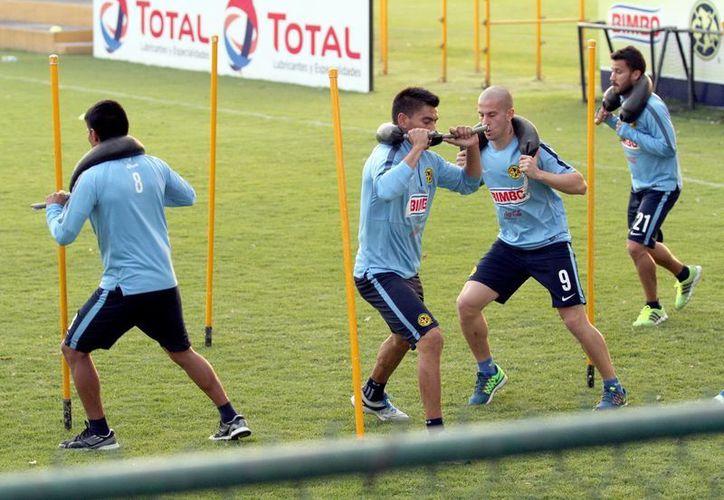 El delantero Darío Benedetto (calvo) entrena al parejo de sus compañeros en un entrenamiento previo al inicio del torneo Clausura 2015. (Foto de archivo de Notimex)