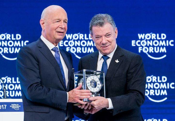 El presidente de Colombia, Juan Manuel Santos, recibe el premio al estadista mundial del año (Global Statesman Award) por lograr un acuerdo con las FARC, de manos del fundador y presidente del Foro Económico Mundial, Klaus Schwab, en Davos, Suiza. (Notimex)