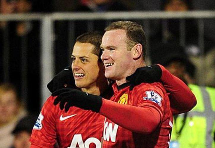 Chicharito felicita a Rooney, tras el gol del jugador inglés. (Agencias)