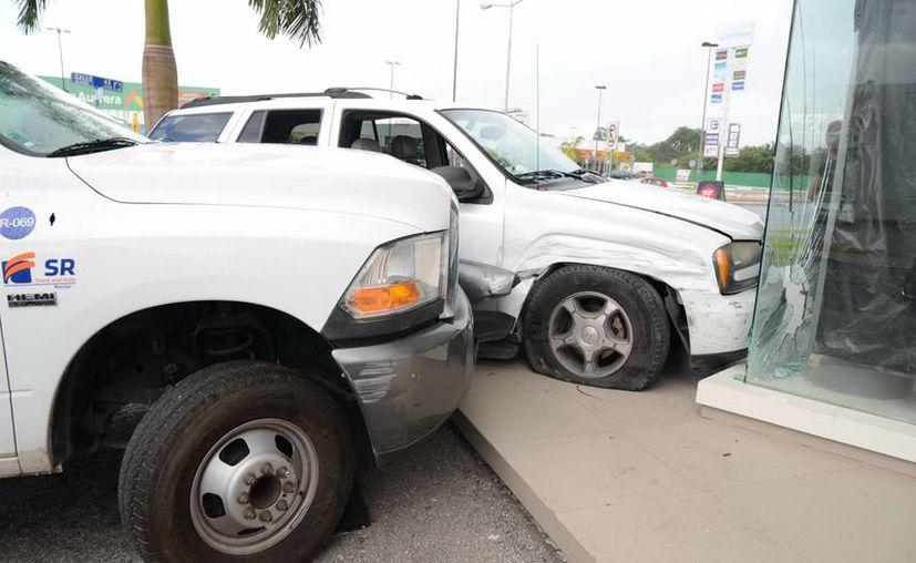 """La camioneta Trail Blazer terminó su loca carrera en el """"aparador"""" de un local, no sin antes chocar contra un camión estacionado. (Milenio Novedades)"""