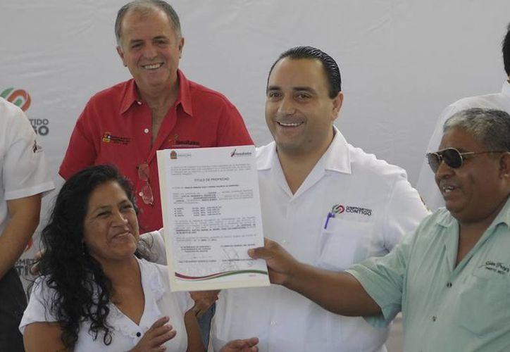 El gobernador con autoridades estatales en la entrega de los títulos de propiedad. (Cortesía/SIPSE)