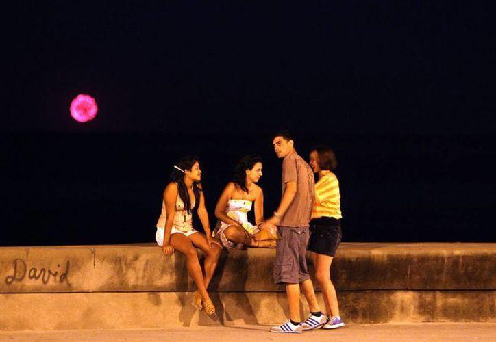 Jóvenes conversan mientras en el fondo se observan los fuegos artificiales lanzados por una flotilla del exilio cubano en el malecón de La Habana, Cuba. (Archivo/EFE)