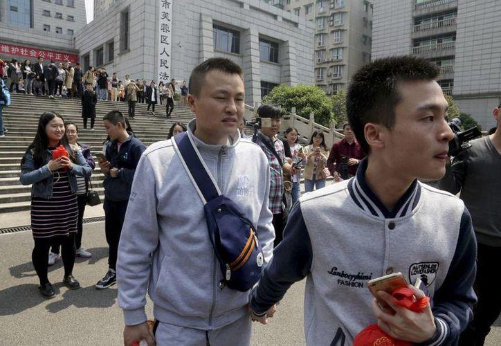 Sun Wenlin, a la derecha, y su pareja Hu Mingliang al salir del tribunal luego que un juez falló contra ellos. (Agencias)