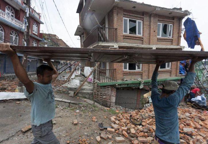 Varios nepalíes participan en la labores de reconstrucción de las viviendas destruidas por los sucesivos terremotos que han asolado Nepal. (EFE)