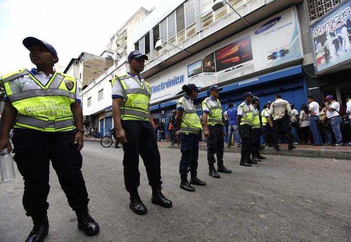 La Policía vigila un sector comercial en Caracas, donde se han disparado las compras debido a que se obligó a comercios de electrodomésticos a bajar sus precios. (AP)
