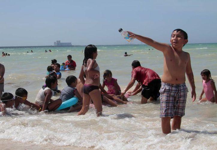 La temporada de verano trae más visitantes y más desperdicios a las playas de Yucatán. Imagen de un grupo de vacacionistas en Progreso, Yucatán. (Óscar Rodríguez/SIPSE)