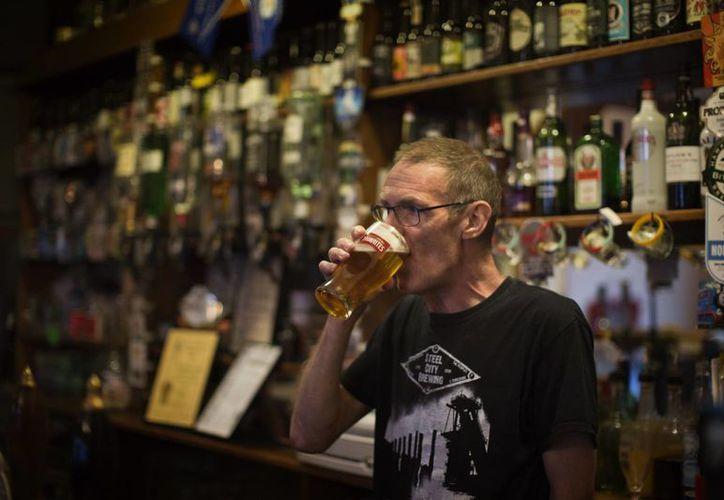 Bram Brammer bebe cerveza en su pub de Peterborough. Brammer se queja de que los inmigrantes no tratan de integrarse y teme que la dinámica generada por la llegada de decenas de miles de extranjeros le haga perder su negocio. (Agencias)