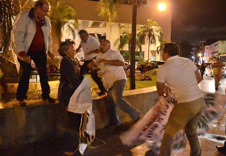 Momento de la agresión que sufrieron ciudadanos de Mérida que se manifestaban frente a un hotel donde se realiza la reunión plenaria de senadores del PRI, en Paseo de Montejo. (Facebook)