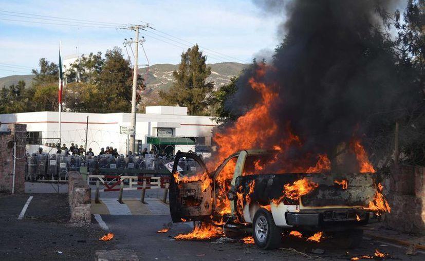 Un camión fue incendiado cerca de las instalaciones del Ejército en Iguala tras ser expulsados de ahí. (AP)