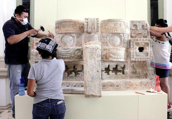 Especialistas trabajan en un enorme mascarón de Chaac que se destacó en la exposición. Imagen de archivo. (Mario Escalante/SIPSE)